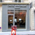 Vue de la vitrine et de l'enseigne à lettres inox et caisson lumineux de l'agence immobilière Castel France à Paris