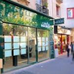 Vue d'ensemble de 3/4 de l'enseigne, du caisson et de la vitrine pour agence immobilière à Paris (Capital Immobilier)